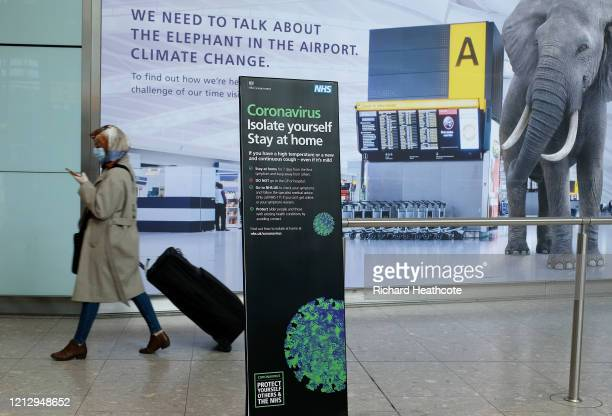 Passengers in face masks pass through arrivals at Heathrow Terminal 5 on March 17 2020 in London United Kingdom Several UK and European carriers are...