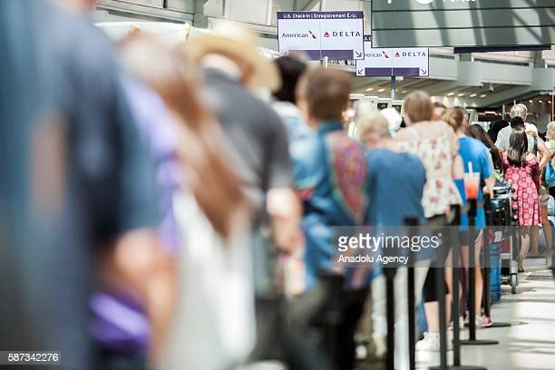 Passengers in line await updates from Delta airline employees at Pearson International airport in Toronto Canada on August 8 2016 Passengers were...