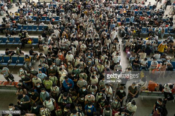passengers in line wearing protective masks at hankou railway station in wuhan - wuhan stock pictures, royalty-free photos & images