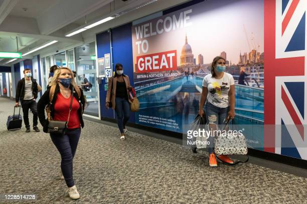 Passengers in protective face masks are seen arriving at London Stansted Airport as the airline industry tries to recover after global Coronavirus...