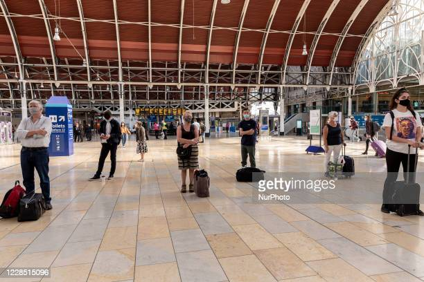 Passengers in protective face masks are seen waiting for their train connections at Paddington, London train station as the United Kingdom is...