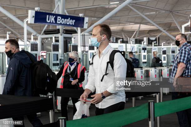 Passengers in protective face masks queue at the passport control after arriving at London Stansted Airport as the United Kingdom is trying to take...