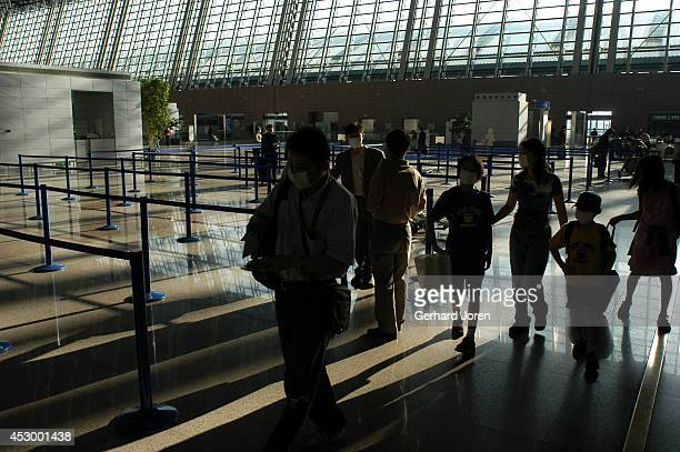 Passengers in the departure hall of the Shanghai Pudong International Airport which opened in October 1999 use masks to help protect against the SARS...