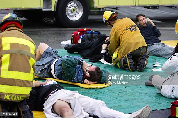 Passengers injured in a commuter train wreck talk on a cell phones while undergoing triage on January 26 2005 in Glendale California The wreck...