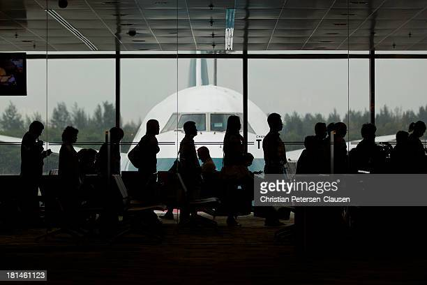 Passengers inside a terminal at Changi airport in Singapore are lining up to board a Cathay Pacific 747-400 airplane bound for Hong Kong.