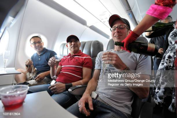 USA Passengers Jordan Scheinfeldt left Mark Hermogeno and Ryan Swedlund right get champaign from comedian and 'air hostess' Pam Ann pour champaign...