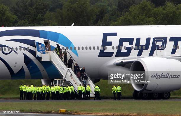 Passengers leave the Egyptair aircraft flying from Cairo to New York after it was diverted to Prestwick Airport Ayrshire after a suspicious note was...