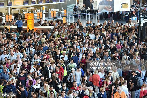 Passengers leave the terminal 1 of the airport of Frankfurt on August 31 as the police clears the airport due to a person who entered the security...
