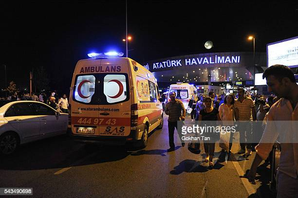 Passengers leave the Turkey's largest airport Istanbul Ataturk after the suicide bomb attacks as ambulances enters June 28 Turkey Three suicide...