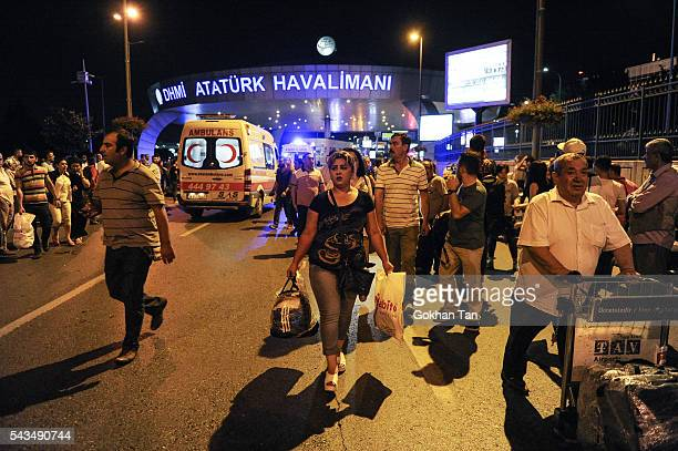 Passengers leave the Turkey's largest airport Istanbul Ataturk after the suicide bomb attacks as ambulances enter to the site June 28 Turkey Three...