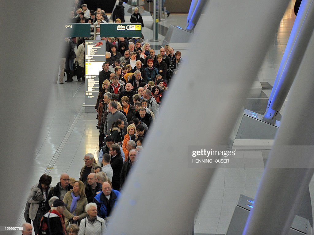 Passengers line up at the airport in Duesseldorf, western Germany, on January 24, 2013