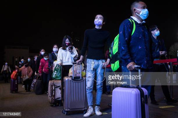 Passengers line up to enter Wuchang railway station on April 72020 in Wuhan Hubei Province China The Chinese government lifted travel restrictions...