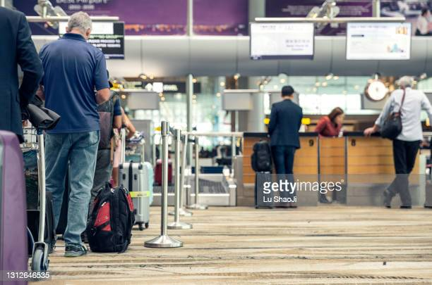 passengers lined up at the airport to check in their luggage. - lining up stock pictures, royalty-free photos & images