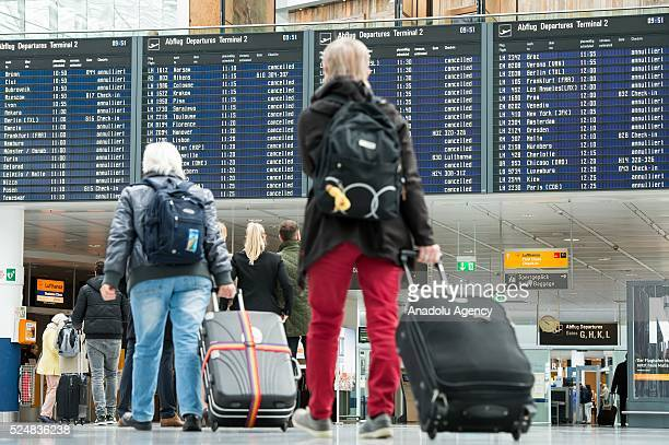 Passengers look at a flight information board showing cancelled flights at the Munich Airport affected by strike action in Munich Germany on April 27...