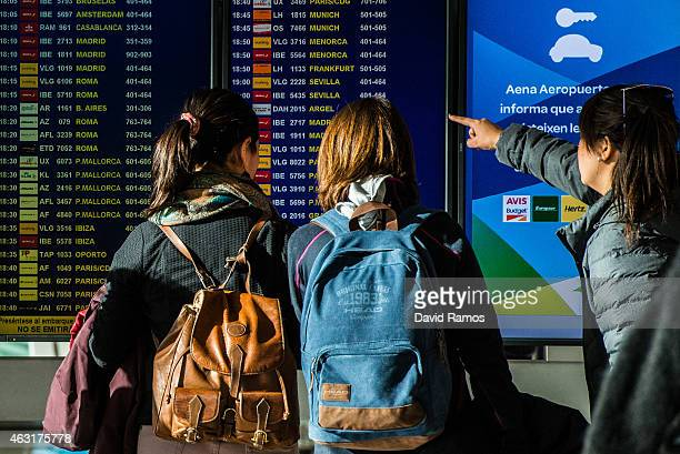 Passengers look at arrivals and departures on a screen at Aena operated Barcelona El Prat International Airport on February 10 2015 in Barcelona...