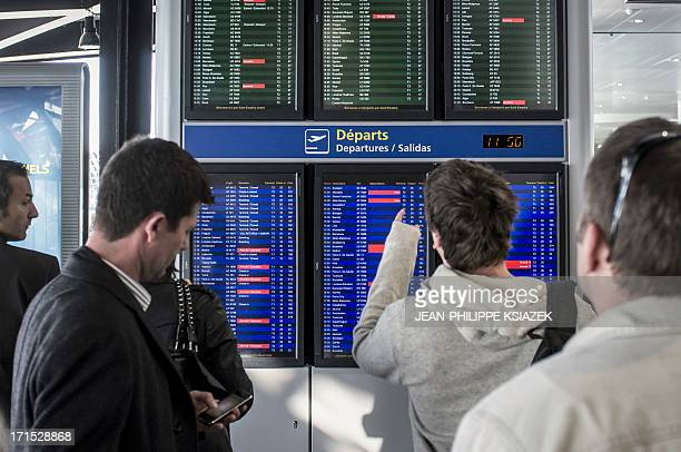 Passengers look at departures screens on April 2 2012 at the SaintExupery airport in Lyon central eastern France on the first day of a strike of air...