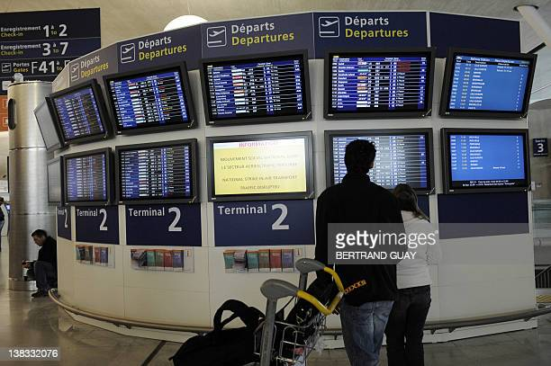 Passengers look at departures screens on February 6 2012 at the Paris international airport of RoissyCharles de Gaulle as major air traffic...