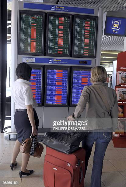 Passengers look at information boards announcing the cancelled flights in red, on April 20, 2010 at the Saint Exupery airport in Lyon, eastern...