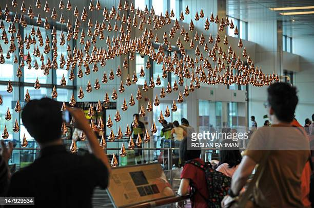 Passengers look at Kinetic Rain reportedly the world's largest kinetic art sculpture hanging in the departure checkin hall in Singapore's Changi...