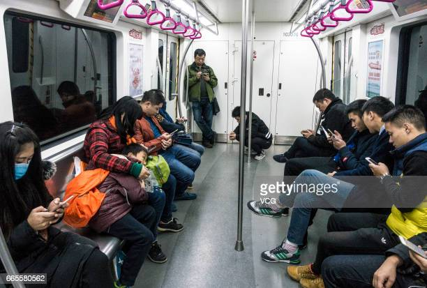Passengers look at smartphones on a subway train on April 6, 2017 in Chengdu, China. China Unicom started to offer free fourth-generation mobile...