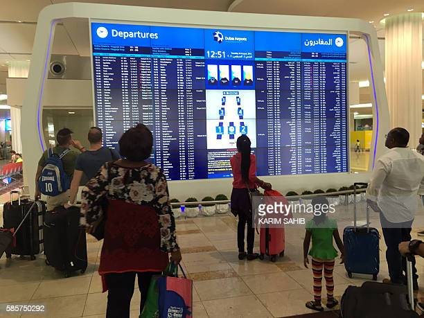 Passengers look at the departures announcement board at Dubai airport a day after an Emirates plane caught fire during a crashlanding on August 4...