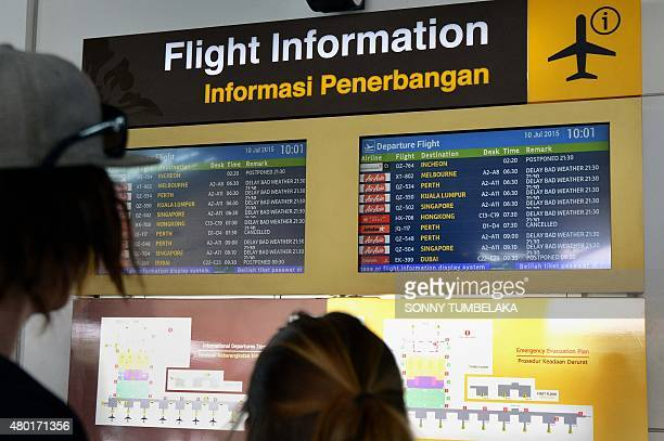 Passengers look at the information board in the international terminal at Bali's Ngurah Rai airport in Denpasar hoping for information of flight...