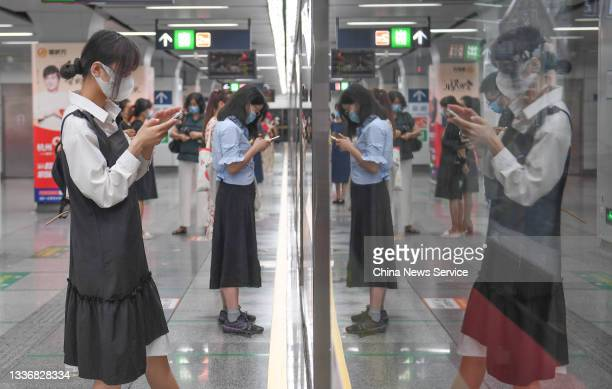Passengers look at their smartphones as they wait for a subway train at a subway station on April 27, 2021 in Hangzhou, Zhejiang Province of China....