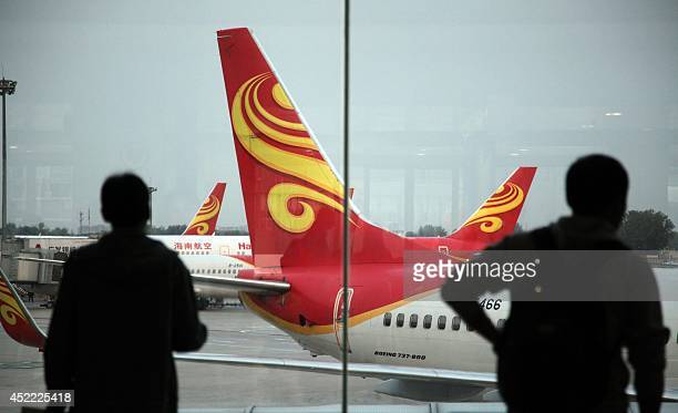 Passengers look on June 12 2014 at planes belonging to China's Hainan Airlines at the gate at Haikou airport in south China's Hainan province Hainan...