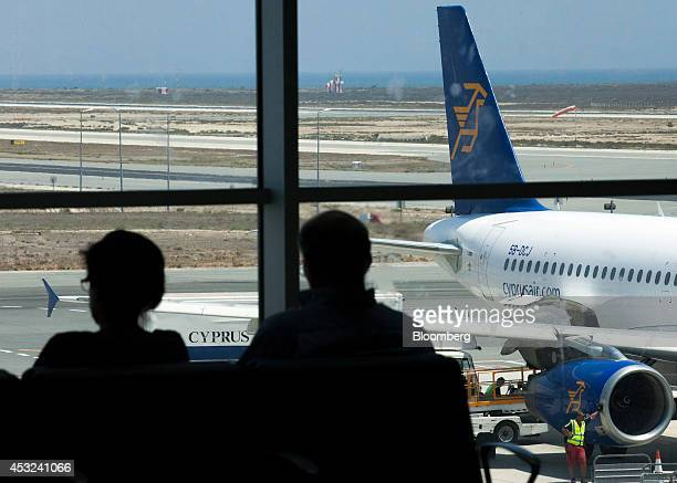 Passengers look out across the runway in the departures terminal while waiting to board a Cyprus Airways Public Ltd flight at Larnaca international...