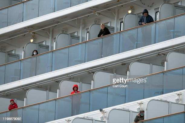 Passengers look out from balconies on the Diamond Princess cruise ship while it is docked at Daikoku Pier where it will be resupplied and newly...
