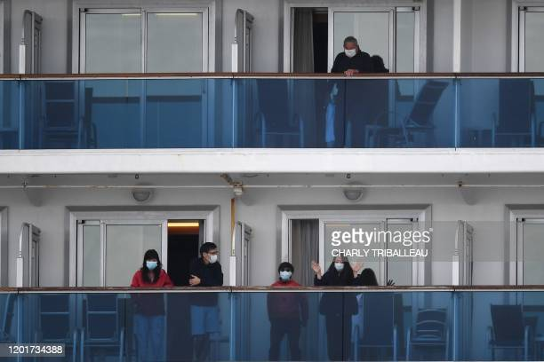 Passengers look out from the balconies of the Diamond Princess cruise ship - in quarantine due to fears of the new COVID-19 coronavirus - as a the...