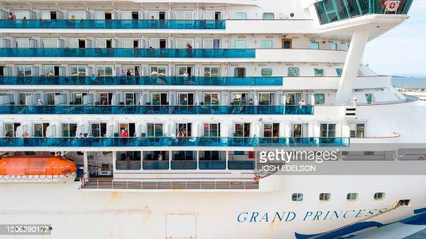 Passengers look out from the Grand Princess cruise ship at the Port of Oakland in Oakland California on March 09 2020 The cruise ship carrying...