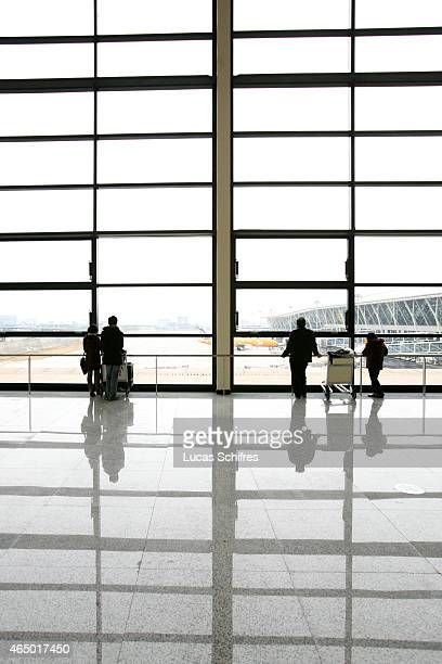 Passengers look out the windows of Shanghai Pudong International airport on January 7 2009 in Shanghai China Shanghai Pudong International Airport in...
