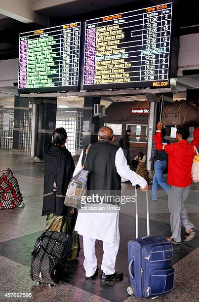 Passengers looking at railway train chart displaying delayed passenger trains at New Delhi Railway Station on a foggy morning on December 18 2013 in...