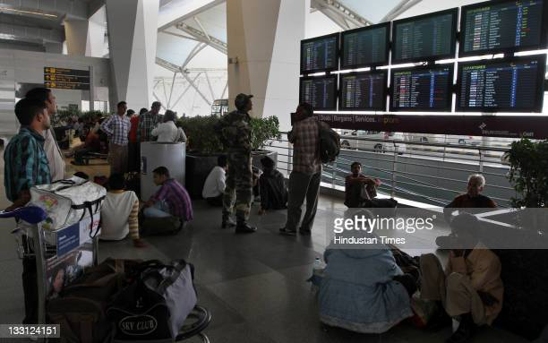 Passengers looking at the display board to know the status of their flight at Terminal 3 in Indira Gandhi International airport in New Delhi India on...