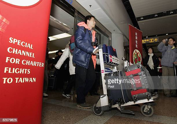 Passengers make their way out of the arrival lounge after arriving on Taiwan's China Airlines plane at Beijing Capital International airport January...