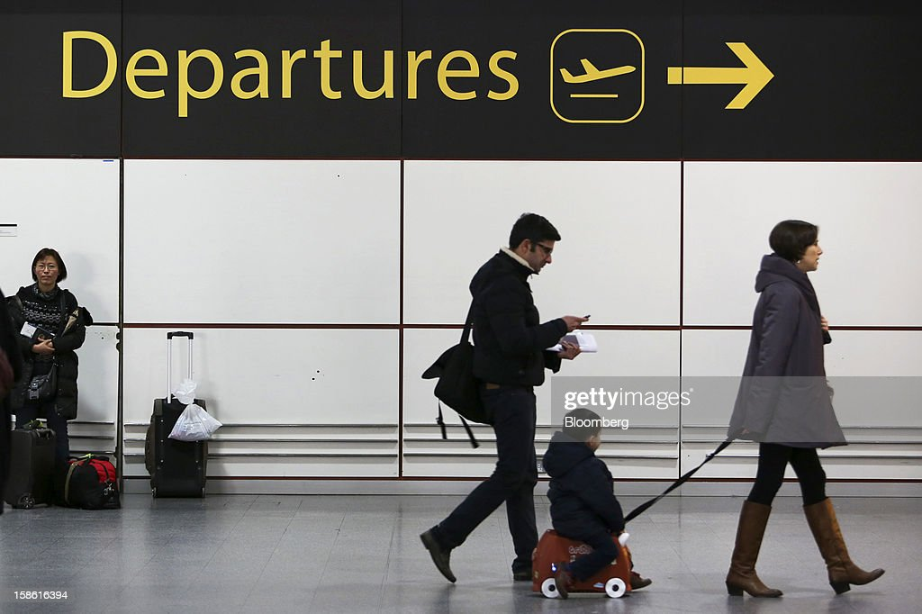 Passengers make their way towards the departures area of the north terminal at Gatwick airport in Crawley, U.K., on Friday, Dec. 21, 2012. U.K. airports predicted today to be the busiest day during the Christmas period, as some Britons opt to spend the holidays abroad and overseas visitors fly out to be with friends and family. Photographer: Chris Ratcliffe/Bloomberg via Getty Images