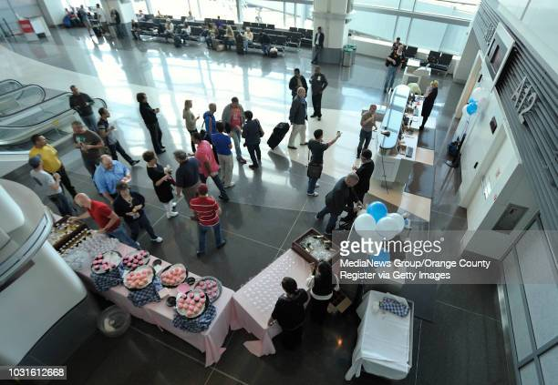 USA Passengers mingle as they drink champaign and eat pink cupcakes at San Francisco International Airport before boarding JetBlue's JetPride flight...