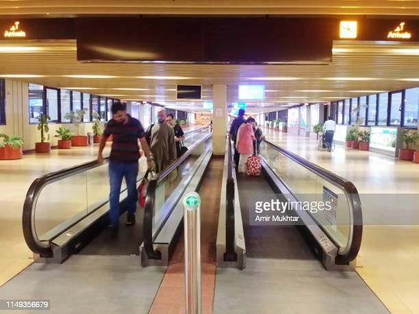Passengers moving while standing on conveyor belt on airport