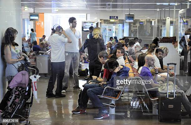 Passengers of a plane whose engine caught fire just before takeoff from Paris' Orly airport wait in a departure lounge prior to take another plane to...