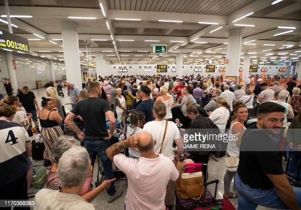 Passengers of British travel group Thomas Cook queue at Son Sant Joan airport in Palma de Mallorca on September 23 2019 British travel group Thomas...