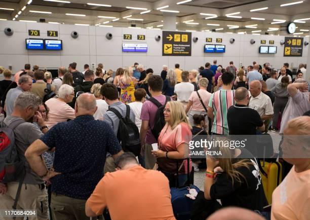 Passengers of British travel group Thomas Cook queue at Son Sant Joan airport in Palma de Mallorca on September 24 2019 Britain has repatriated ten...