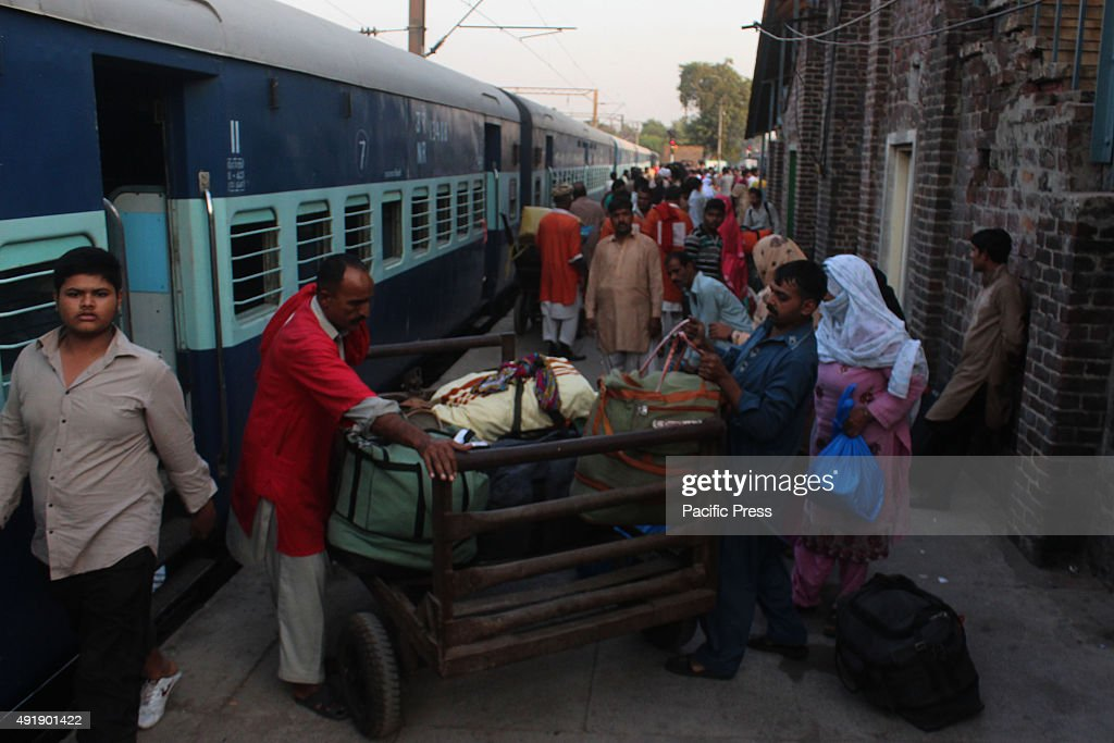 Passengers of Samjhuata express carry their luggage upon arriving in Lahore railway station after India refused their entry to Wagah Border due to...
