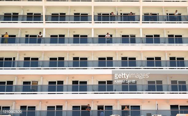 Passengers of the AIDA prima the flagship of AIDA Cruises are pictured after it docked at Port Rashid in the Emirati city of Dubai on April 22 2020...