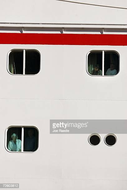 Passengers of the Carnival Liberty Cruise ship look out the window of their rooms as they wait to disembark from the ship at Port Everglades on...
