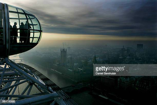Passengers of the London Eye watch the London skyline as smoke is seen in the distance on December 11 2005 in London England A series of explosions...