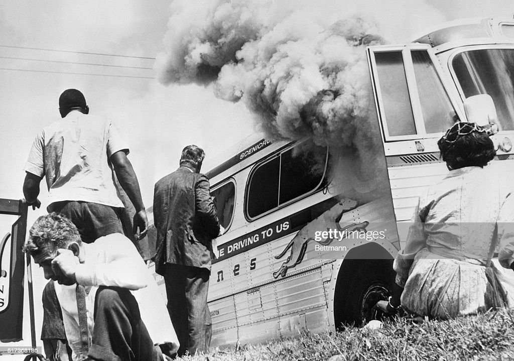 Passengers of this smoking Greyhound bus, some of the members of the 'Freedom Riders,' a group sponsored by the Congress of Racial Equality (CORE), sit on the ground after the bus was set afire 5/14, by a mob of Caucasians who followed the bus from the city. The mob met the bus at the terminal, stoned it & slashed the tires, then followed the bus from town. BPA2# 47.