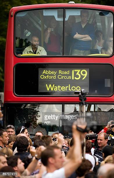 Passengers on a bus look out as beatles fans walk on the zebra crossing used in the photoshoot for the Beatles album Abbey Road outside the Abbey...