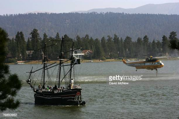 Passengers on a pirate ship-themed boat watch as a Carson Super S-61 firefighting helicopter draws up water from Big Bear Lake while fighting the...