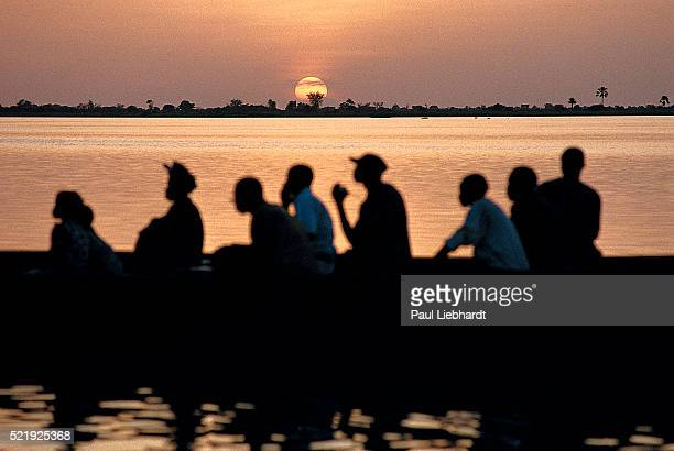 Passengers on a piroque at sunset on the Niger River in Mali